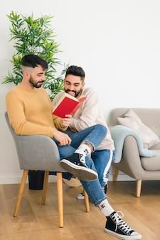 リビングルームで本を読んで笑顔の同性愛若いカップル