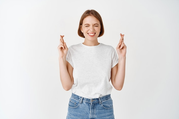 Улыбающаяся обнадеживающая девушка закрывает глаза и скрещивает пальцы на удачу, загадывает желание или молится, стоя в футболке и джинсах на белой стене