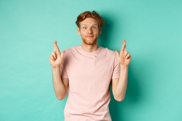 ターコイズブルーの背景の上に立って、願い事をし、幸運のために指を交差させ、何か良いことを期待して、赤い髪の希望に満ちた男の笑顔