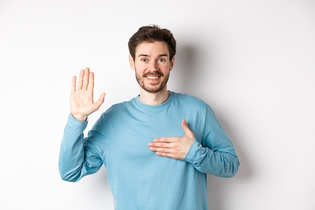 미소 짓는 호 젠트 남자 팔을 들고 마음에 손을 잡고, 약속을 진실을 말하고, 맹세하거나 맹세하고, 흰색 배경 위에 서서