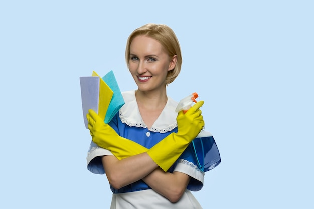 Smiling housemaid is armed with items for cleaning