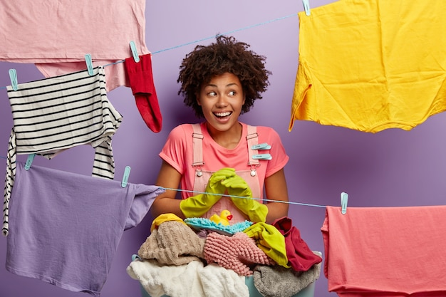 Smiling housewife hangs wet clean clothes to dry on rope with clothespin, wears rubber protective gloves, busy with housework at weekend, isolated over purple studio wall, performs home duties