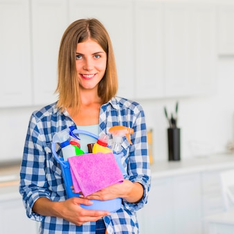 Smiling housewife holding cleaning equipment in hands