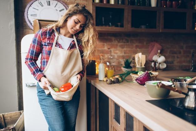 Улыбающаяся домохозяйка держит в фартуке свежие овощи