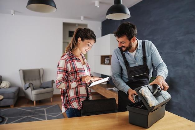 Улыбающаяся домохозяйка платит ремонтнику за планшет, пока ремонтник собирает свои инструменты.
