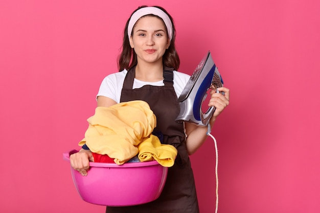 Smiling housewife in white t shirt and brown apron, being ready ironing, holding basin with clean clothes doing housework isolated on pink background.