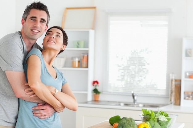Улыбающийся муж и жена обнимаются