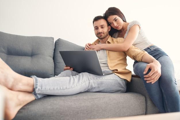 웃고 있는 남편과 아내가 집에서 함께 노트북으로 영화를 보고 있다