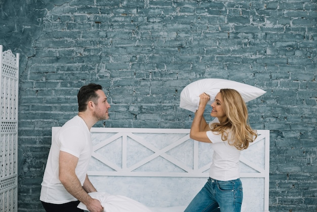 Smiling husband and wife doing pillow fight on bed