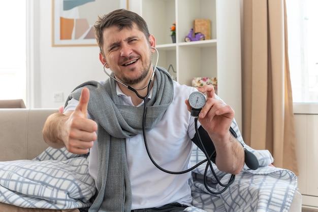 Улыбающийся больной славянский мужчина с шарфом на шее измеряет свое давление сфигмоманометром и поднимает палец вверх, сидя на диване в гостиной