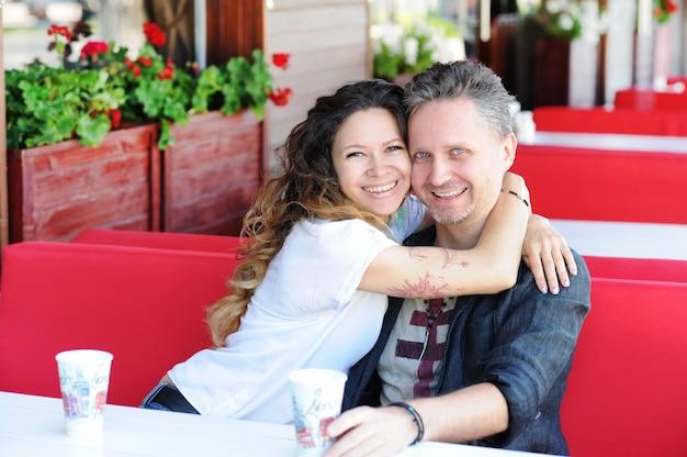 屋外のストリートカフェに座っている愛のカップルの笑顔