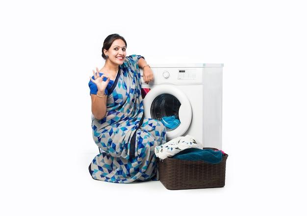 Улыбающаяся индийская азиатская домохозяйка в сари стоит возле стиральной машины с корзиной одежды