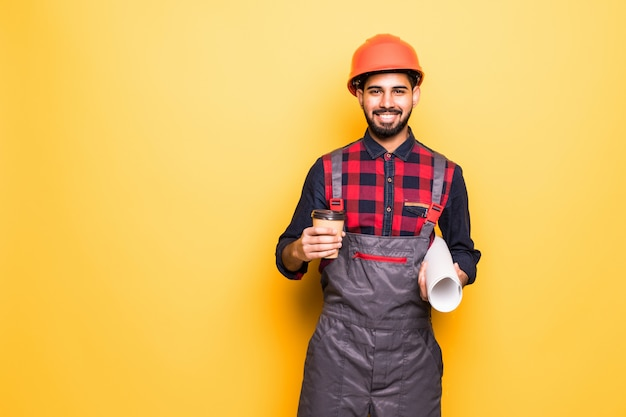 Smiling indian engineer in safety vest holding blueprints and coffee to go isolated on yellow space