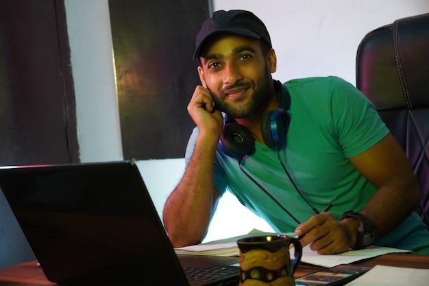 노트북 컴퓨터를 사용하거나 온라인으로 공부하는 웃고 있는 인도 남자
