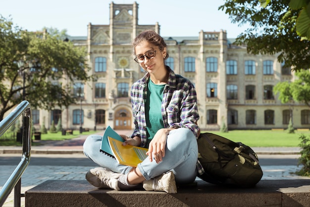 Smiling indian student girl sitting near college. happy young woman in glasses with books.