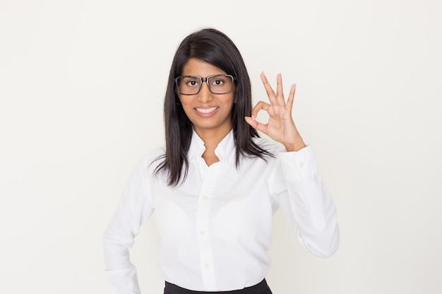 Улыбается индийская женщина в формальной одежде и очки, показывая хорошо жест.
