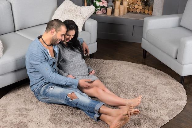 수염을 가진 남자와 벽난로가있는 거실의 카펫에 포옹에 앉아있는 그의 갈색 머리 임신 한 아내의 웃는 국제 커플