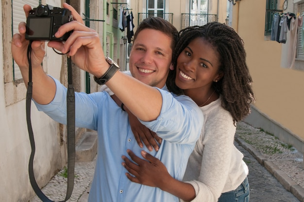 Smiling interracial couple taking selfie photo in street