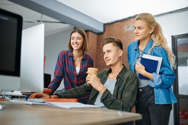 Smiling it specialists works on computers in office. web programmer or designer at workplace, creative occupation. modern information technology, corporate team