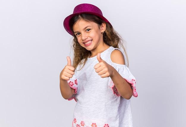 Ragazza caucasica piccola sorridente con i pollici viola del cappello del partito isolati sulla parete bianca con lo spazio della copia