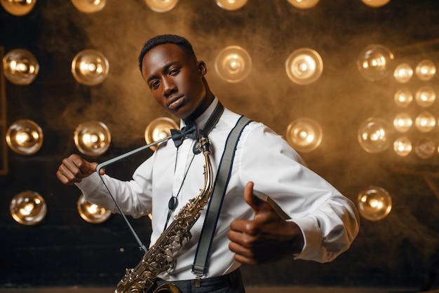 Улыбающийся джазовый исполнитель с саксофоном на сцене