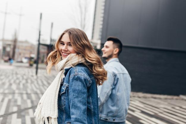 Улыбающаяся веселая девушка, оглядывающаяся через плечо во время прогулки по городу с парнем. открытый выстрел приятной молодой женщины в белом связанном шарфе, наслаждаясь свиданием.