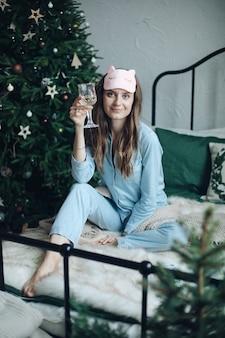 Sorridente donna allegra in pigiama blu e maschera per dormire seduto sul letto con un bicchiere di champagne. natale.