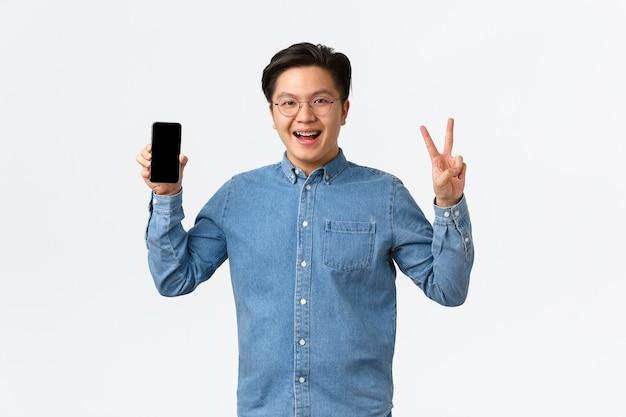 スマートフォンの画面とエンドウ豆を示す眼鏡と中かっこで笑顔の楽しいアジア人男性フリーランサーの学生...