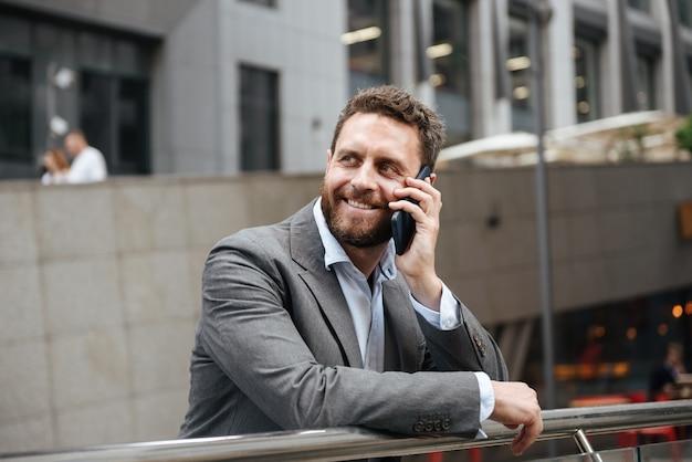 事務所ビルの近くに立っている間、携帯電話で話す灰色のスーツでうれしそうなビジネス男の笑みを浮かべてください。