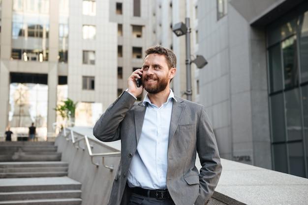モダンなビジネスセンターの外の階段を降りながら携帯電話で話す灰色のスーツのうれしそうなビジネス男の笑みを浮かべてください。