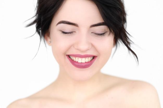 Улыбающаяся радостная довольная женщина на белой стене.