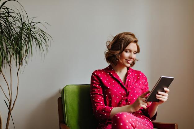 Sorridente donna allegra in indumenti da notte utilizzando la tavoletta digitale. tiro al coperto di donna in pigiama rosso che tiene gadget.