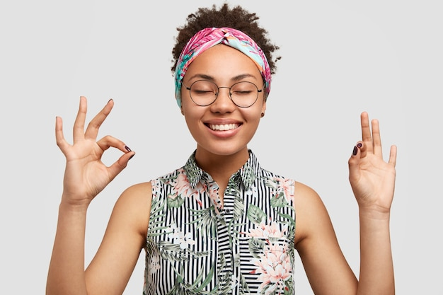 Smiling joyful young woman student satisfied with results of passed exam, shows okay sign, smiles sincerely