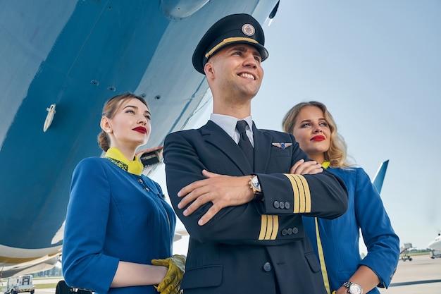 Улыбающийся радостный кавказский летчик и две симпатичные молодые женщины в форме смотрят вдаль