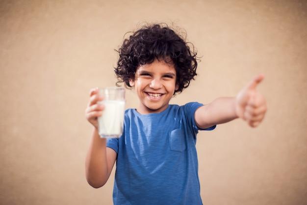 Улыбающийся малыш мальчик держит стакан молока и показывает большой палец вверх жест. концепция детей, здравоохранения и питания