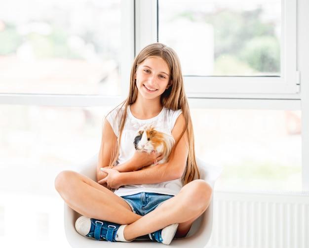 Улыбающаяся девочка малыш держит симпатичную морскую свинку