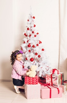 크리스마스 트리 실내와 하얀 테 디 베어를 들고 웃는 꼬마 소녀. 어린 시절.