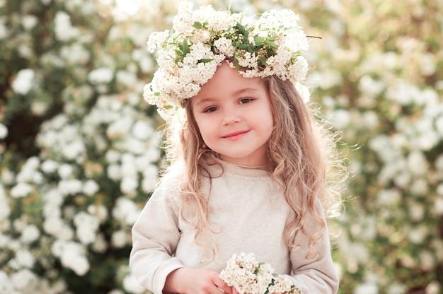 花の背景の上の笑顔の子供の女の子