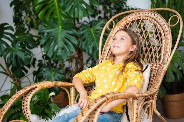 Улыбающаяся девочка малыша отдыхает на кресле-качалке дома