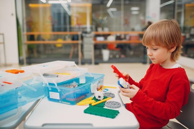 Улыбающийся ребенок маленький мальчик детский конструктор, проверяющий техническую игрушку, детская робототехника, конструктор, сборка ...
