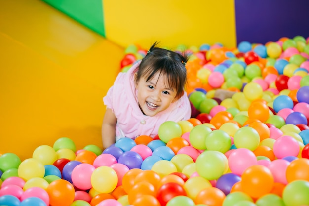 Smiling kid playing in the colorful balls pool.