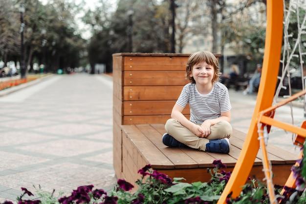Улыбающийся ребенок сидит на деревянной скамейке в городском парке городской ребенок мальчик выходные осень на открытом воздухе