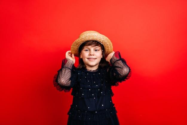 Smiling kid in straw hat. laughing little girl posing in black dress.