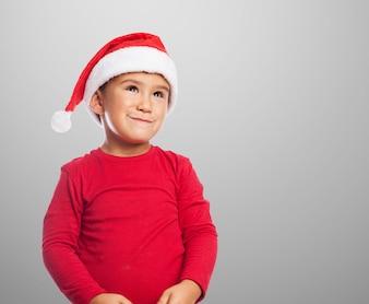 Улыбаясь мальчик носить шляпу Санта