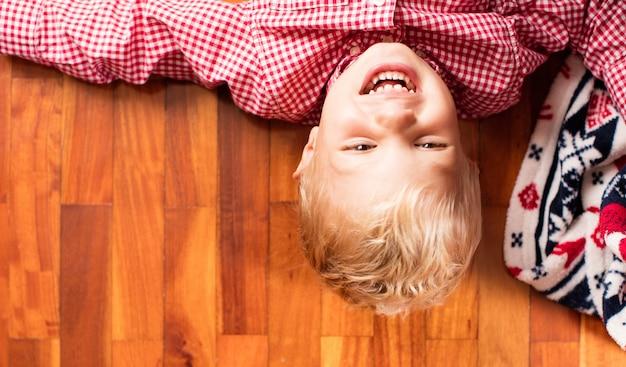 Sorridente bambino sul pavimento di legno