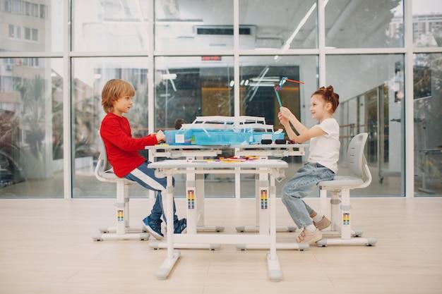 Улыбающиеся дети мальчик и девочка детский конструктор проверяют техническую игрушку детская робототехника конструктор задницу ...