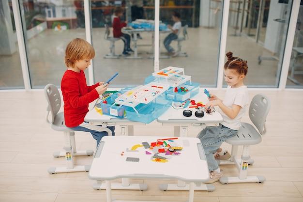Улыбающиеся дети мальчик и девочка детский конструктор, проверяющий техническую игрушку. детский конструктор робототехники собирает робота.