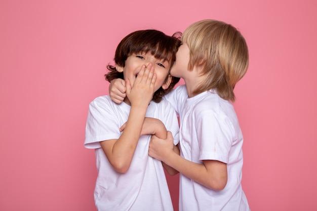Ragazzi dolci adorabili svegli sorridenti del bambino dei bambini su baackground rosa