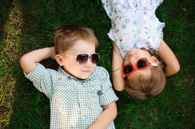Smiling kids at the garden in sunglasses