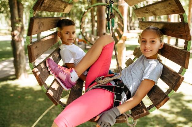 機器で笑顔の子供たちはロープパーク、遊び場に登ります。吊橋に登る子供たち、極端なスポーツアドベンチャー